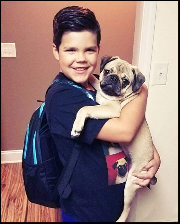A very fine young man with his very fine young pug! - Fawn Pug Puppies | A dog can't think that much about what he's doing, he just does what feels right.